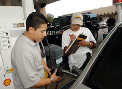 ニューメキシコ州サンタフェで車にガソリンを入れながら、有権者登録するアルフォンソ・マルチネス(© AP Images/Jeff Ceissler)