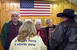 典型的な小さな町の党員集会で候補者について議論するアイオワ州民(© AP Images)