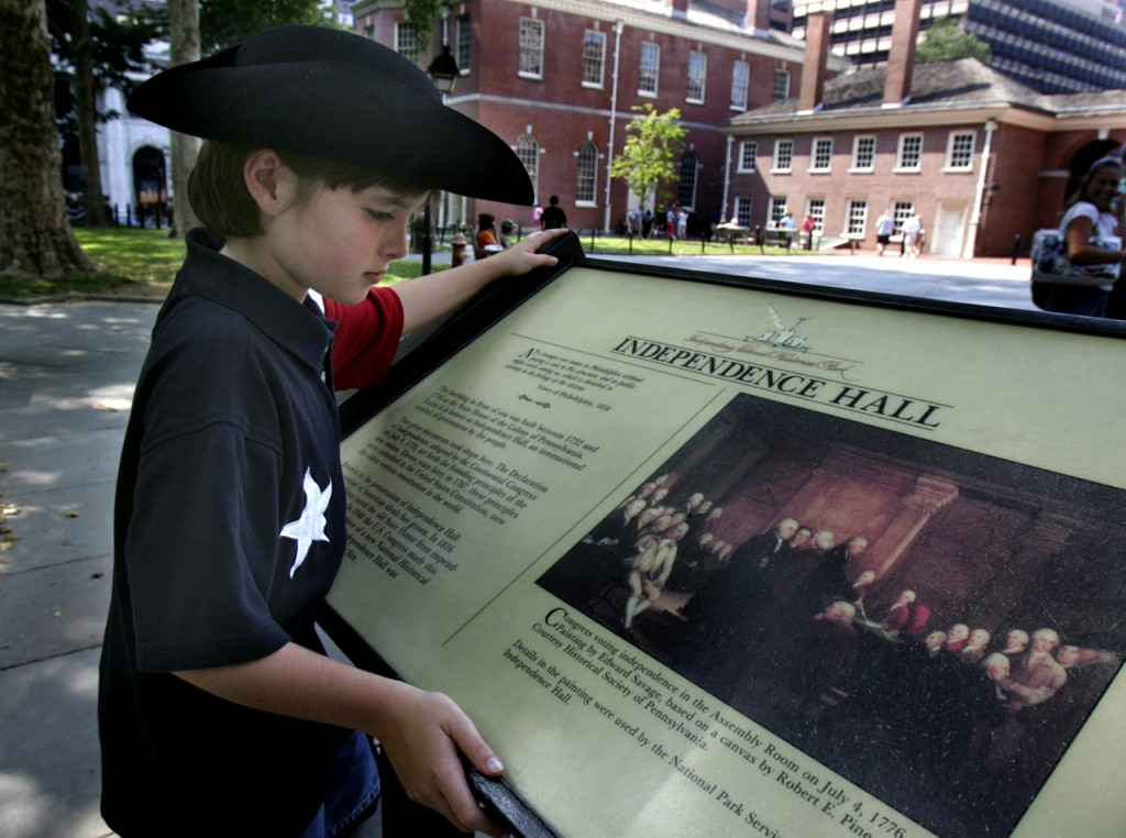 A young boy reads about Independence Hall, where the Declaration of Independence was adopted in 1776. The Independence National Historical Park attracts more than 3 million visitors a year. (AP Photo/Rusty Kennedy)