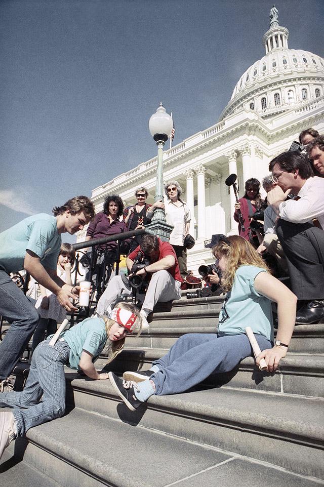 脳性まひを患った8歳の少女が、連邦議会議事堂前の階段を自力で登っている。1990年3月のデモで (AP Photo/Jeff Markowitz)