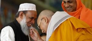 チベットの宗教指導者ダライ・ラマ(手前右)が、イスラム教の導師モハメド・ウスマン(同左)の顎ひげをふざけて引っ張る様子を見守るヒンズー教の導師シブラトリ・デシケンドラ (AP Images)