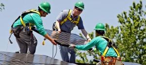 建築作業員と一緒に太陽光パネルを設置するマイケル・ベネット米上院議員 (中央)(© AP Images)
