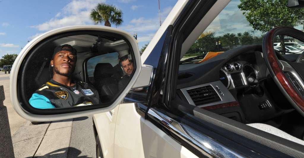 フロリダ州ジャクソンビルで配車サービス「ウーバー」を宣伝するアメリカンフットボールのスター選手アレン・ロビンソン (© AP Images)