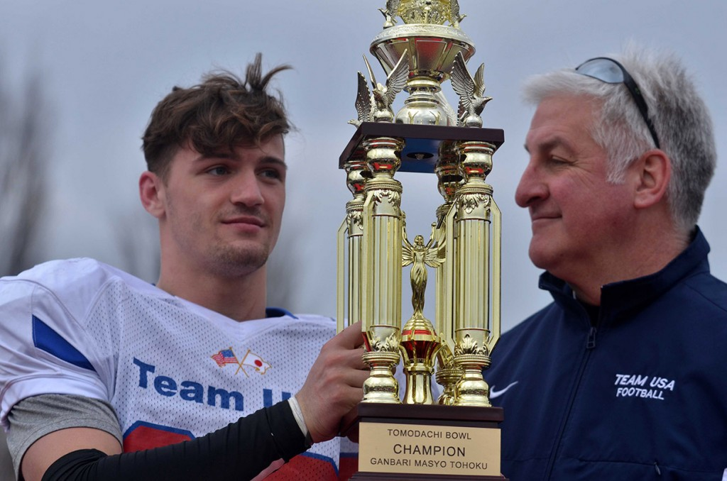 Photo by Dave Ornauer March 13, 2016 To the victors go the spoils. Dominic Santanelli of Kadena High School on Okinawa and Team USA head coach Tim Pujol of Yokota High School in Japan pose with the Tomodachi Bowl champion's trophy