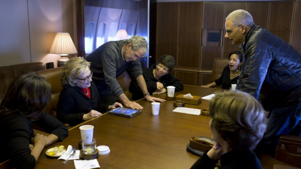 Aboard Air Force One, former President George W. Bush shows photos of his paintings to first lady Michelle Obama, former Secretary of State Hillary Rodham Clinton, Obama staff and Cabinet members, and Laura Bush. (White House)