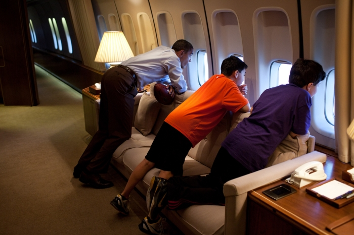 President Obama looks out a window of Air Force One with the sons of an aide during a flight to Hawaii in 2011. (White House)