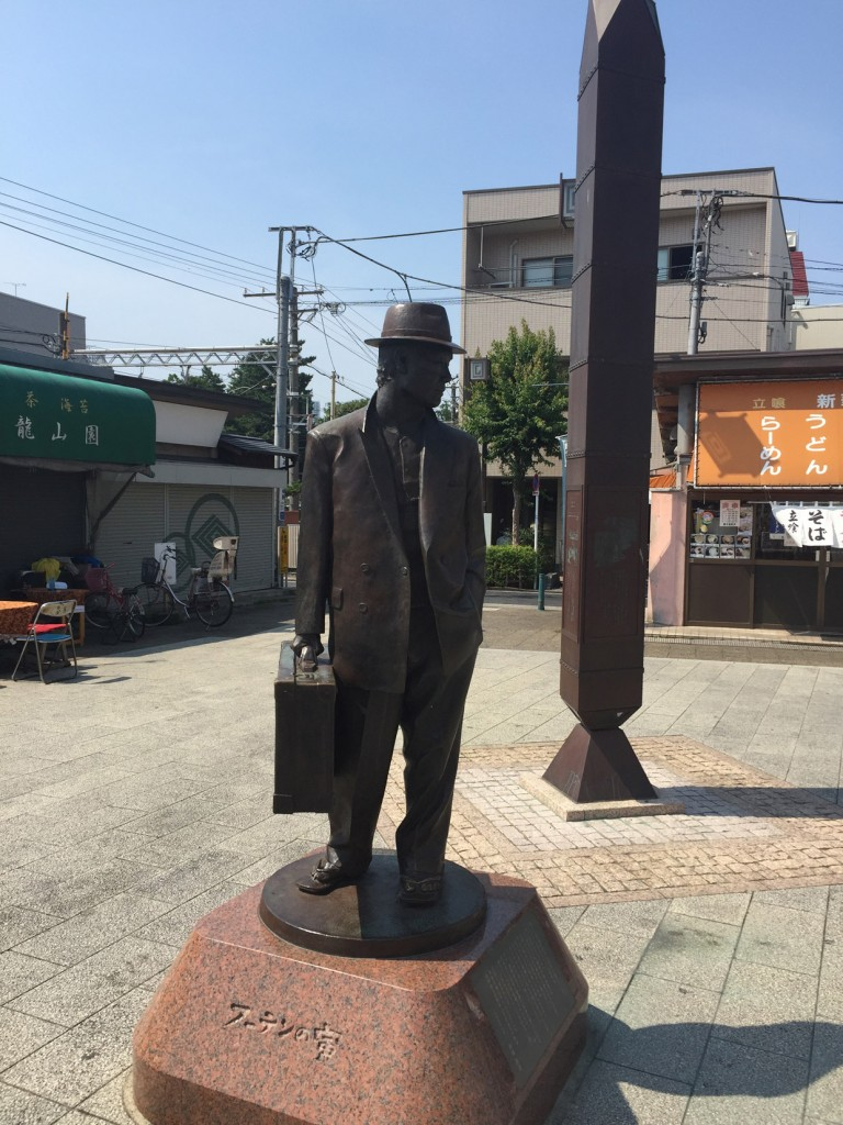 柴又駅前に建つ寅さんの銅像。足元には山田洋次監督による寅さんの故郷への思いが刻まれている。