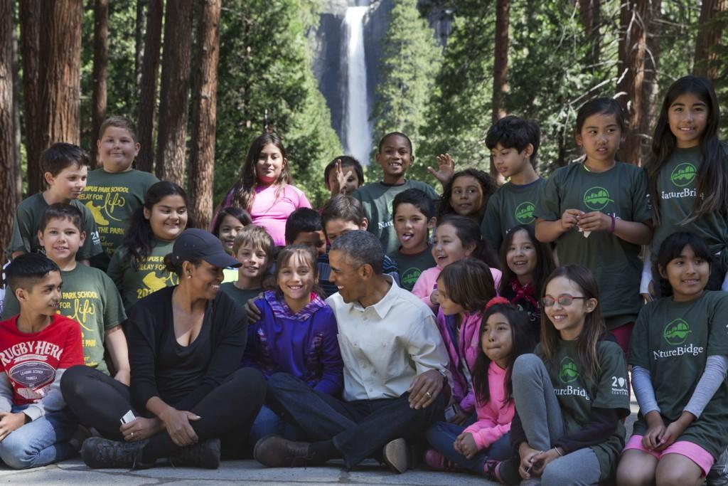 """2016年6月18日にヨセミテ国立公園で開催された """"Every Kid In a Park"""" のイベントに参加する子どもたちと記念撮影するオバマ大統領とミシェル夫人 (AP Photo/Jacquelyn Martin)"""