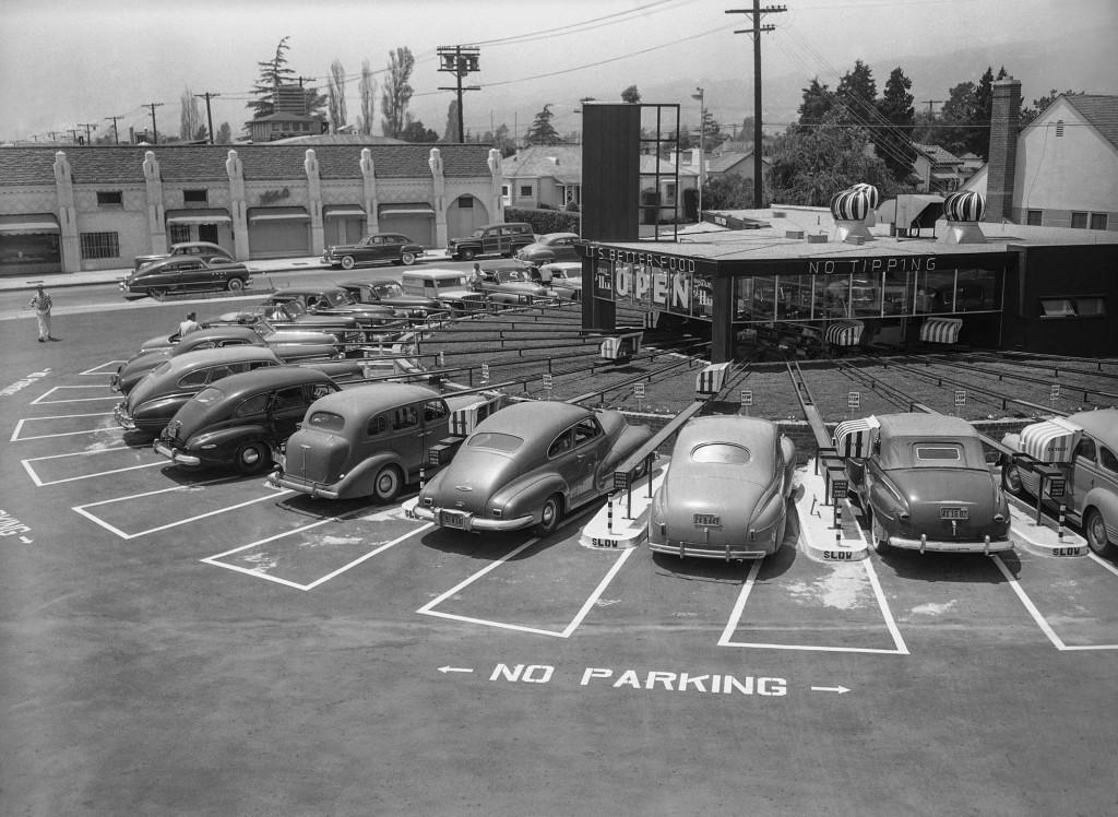 1949年、ロサンゼルスの最新ドライブイン・レストランの様子。電動ケーブルカーで料理が運ばれる (© AP Images)