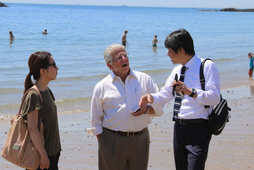 ビーチでボストン日本協会のグリーリ氏(中央)と話す京丹後市の木村嘉充氏(右)と宗原めぐみ氏(左)