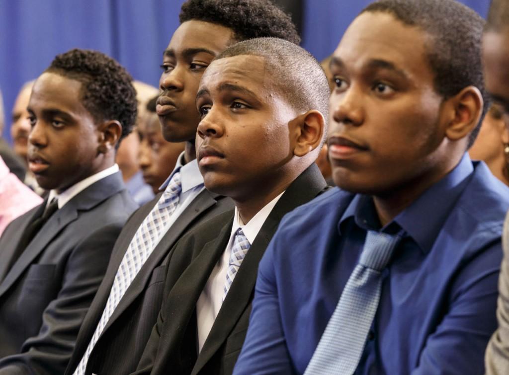 オバマ大統領の「マイ・ブラザーズ・キーパー」イニシアチブについてのスピーチに聞き入るアフリカ系アメリカ人の若者たち (© AP Images)