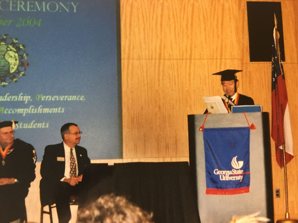 Suga delivering a speech at his graduation ceremony at Georgia State University.
