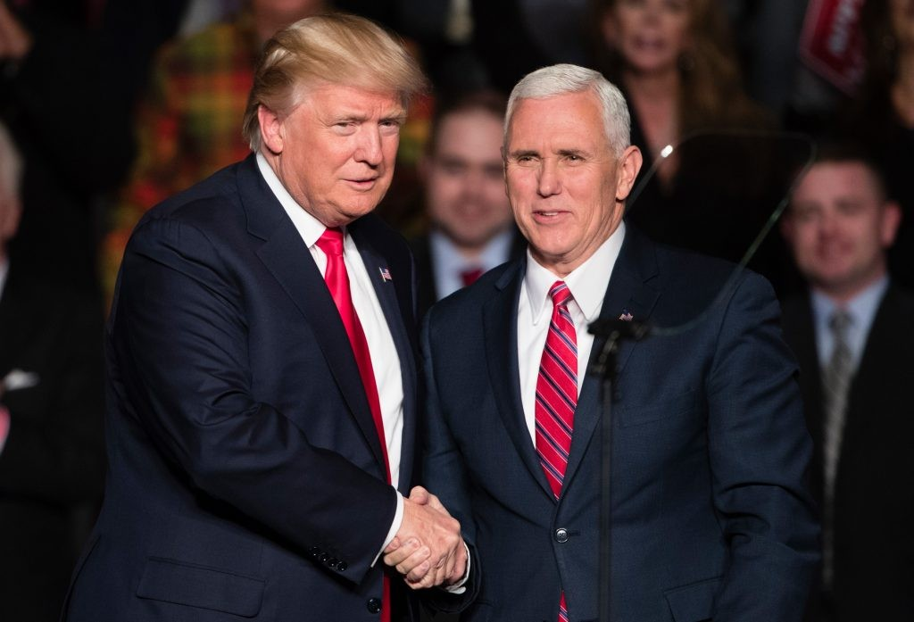 President Donald Trump, left, shakes hands with Vice President Mike Pence. (© AP Images)