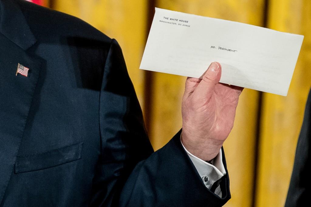 オバマ大統領からの手紙を掲げるトランプ大統領 (© AP Images)