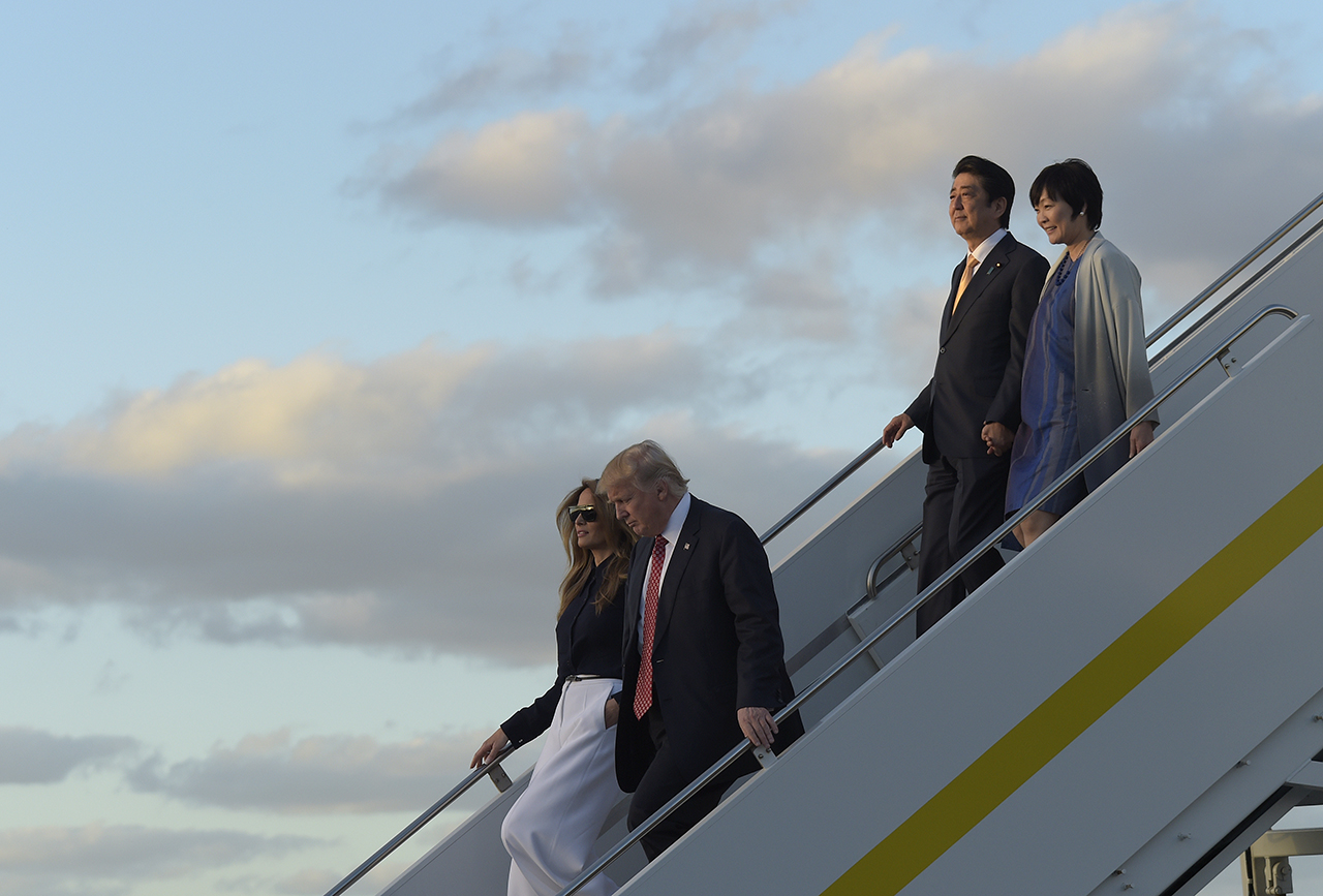 President Donald Trump and first lady Melania Trump, left, and Japanese Prime Minister Shinzo Abe and his wife Akie Abe, right, walk down the steps of Air Force One at West Palm Beach International Airport in West Palm Beach, Fla., Friday, Feb. 10, 2017. The Trumps are hosting the Abes at their Mar-a-Lago estate in Palm Beach for the weekend. (AP Photo/Susan Walsh)