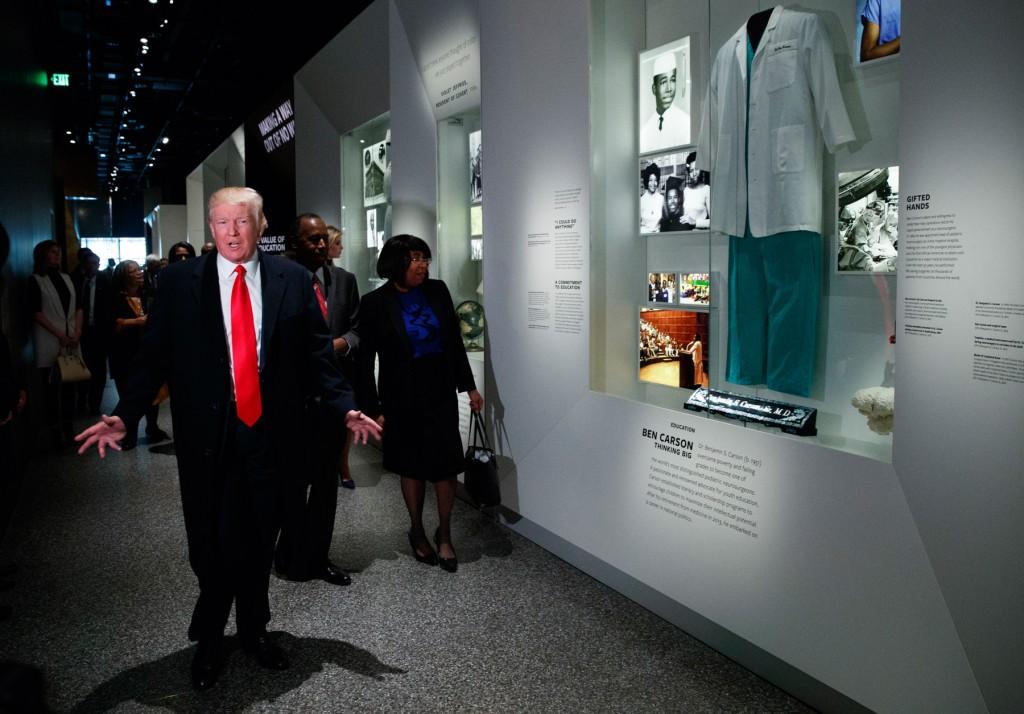住宅都市開発長官に指名したベン・カーソン博士に関する展示コーナーを訪れたトランプ大統領。カーソン夫妻が同行した  (© AP Images)