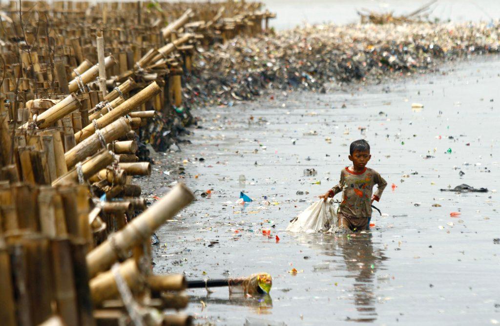 インドネシア・ジャカルタの漁村で廃棄物からお金に換えられる物を集める子ども (© Solo Imaji/Barcroft Media via Getty Images)