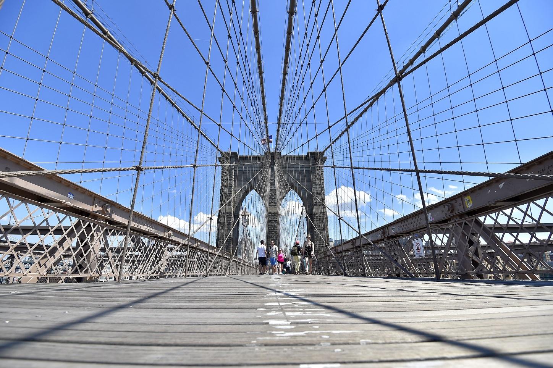 2017年7月2日、ニューヨークのブルックリン橋を渡る人たち (© Loic Venance/AFP/Getty Images)