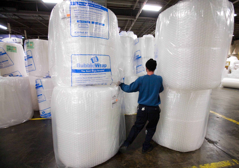 ニュージャージー州サドルブルックにあるシールドエア社の建物内で、巨大なバブルラップのロールを運ぶ従業員 (AP Photo/Christopher Barth, File)