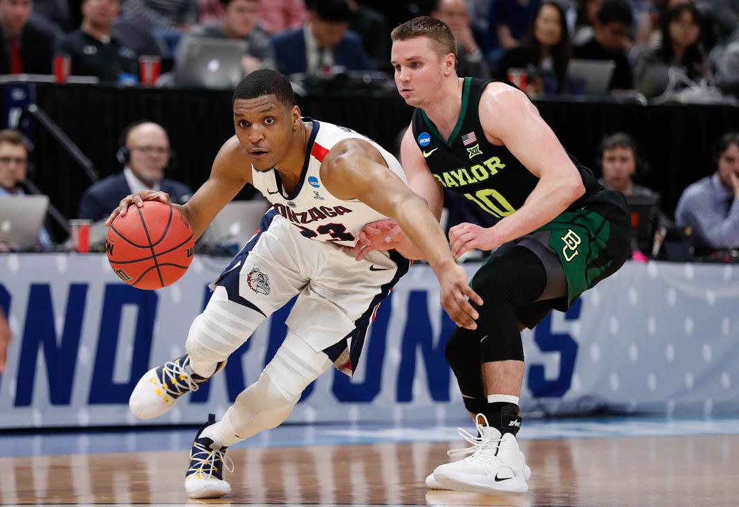 ソルトレークシティーで行われた今年のNCAA男子バスケットボールトーナメント。試合中ドリブルでベイラー大学のマカイ・メイソン選手をかわすゴンザガ大学のザック・ノーベル選手 (© Jeff Swinger/AP Images)