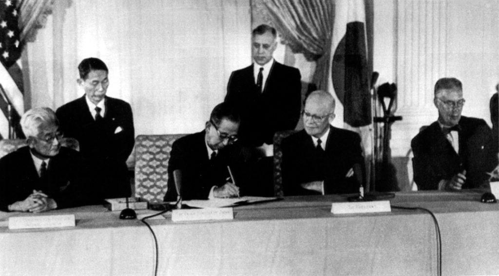 ワシントンにて1960年1月19日、改定された日米安全保障条約に署名する岸信介首相(中央左)。中央右はドワイト・アイゼンハワー大統領 (© Robert M. Baer/AP Images)