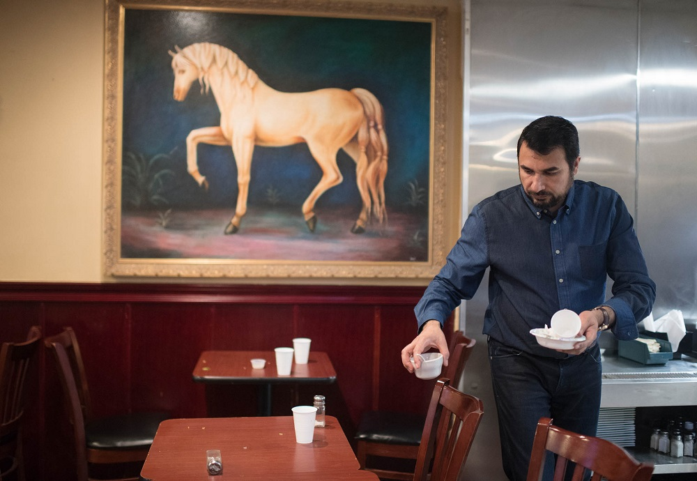Kazi Mannan in restaurant clearing table (© Marvin Joseph/The Washington Post/Getty Images)