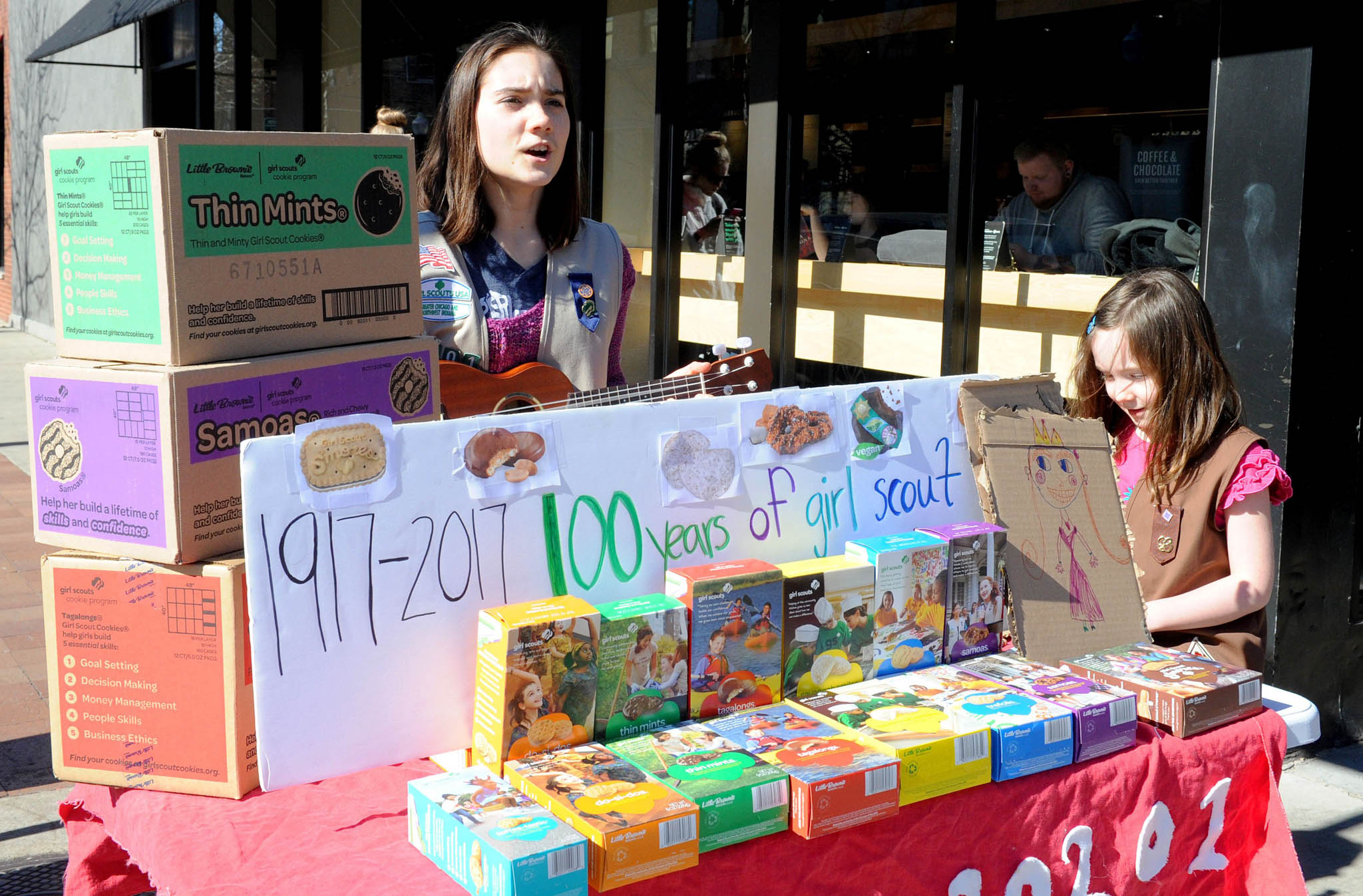 Girl Scouts get creative with their marketing techniques. Molly Sheridan, 13, plays a ukulele to attract customers to her cookie stand in Chicago in 2017. (© Nova Safo/AFP/Getty Images)