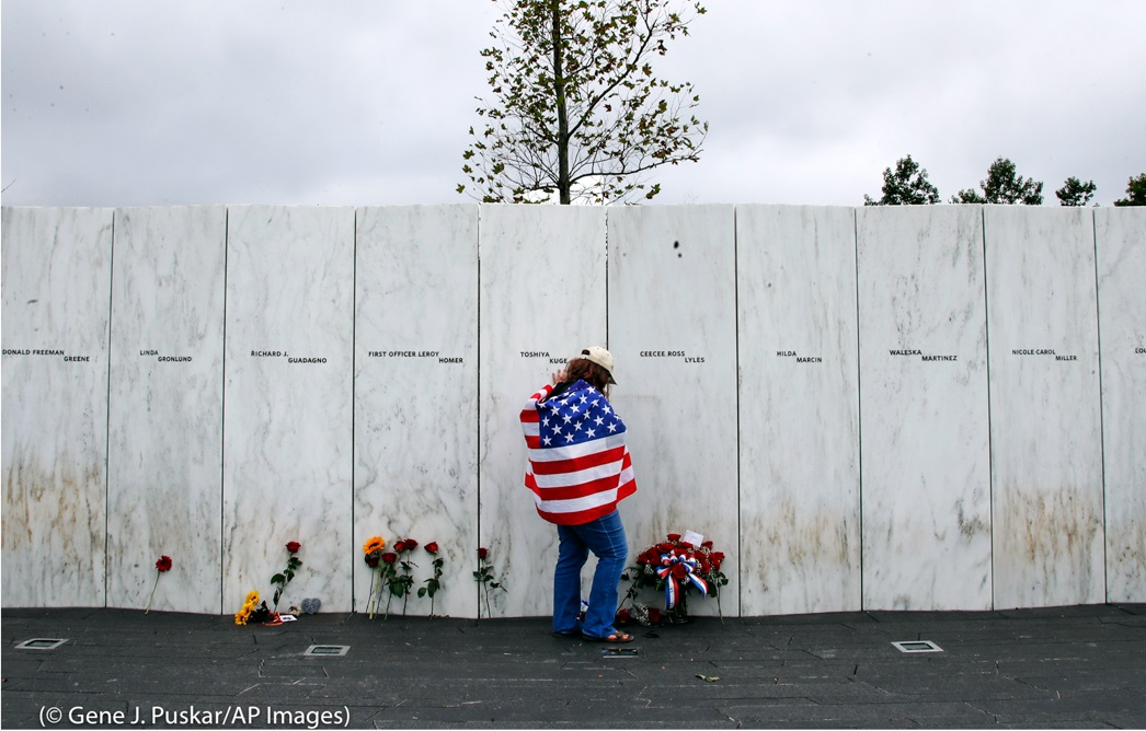 亡くなった40人の名前が刻まれた慰霊碑の前で、女性が哀悼の意を捧げている。