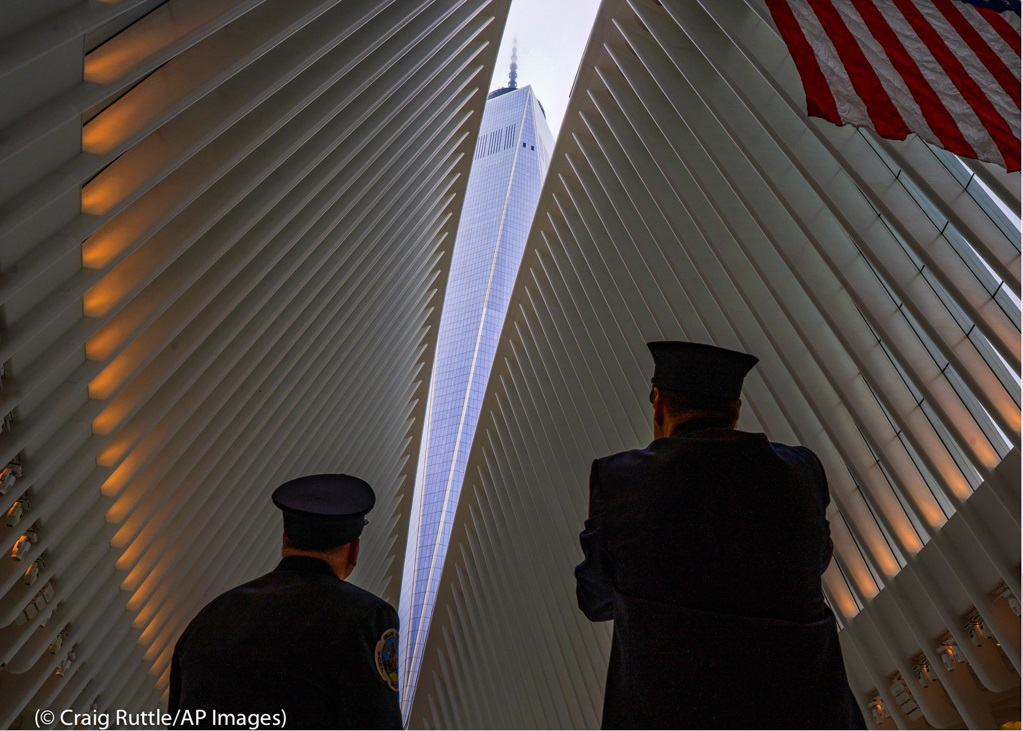 Two members of the New York City Fire Department look toward One World Trade Center through the open ceiling of the Oculus, part of the World Trade Center transportation hub in New York City. The ceiling window was opened just before 10:28 a.m., marking the moment that the North Tower of the World Trade Center collapsed on September 11.