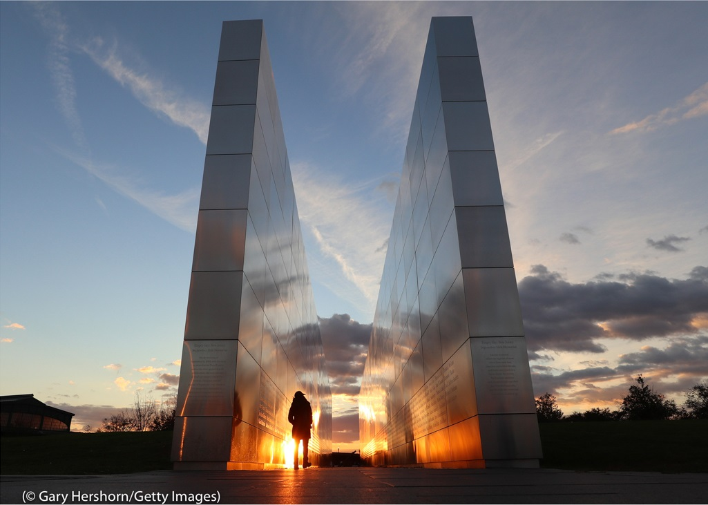 A person walks through the 9/11 Empty Sky Memorial in Liberty State Park in Jersey City, New Jersey, as the sun sets.