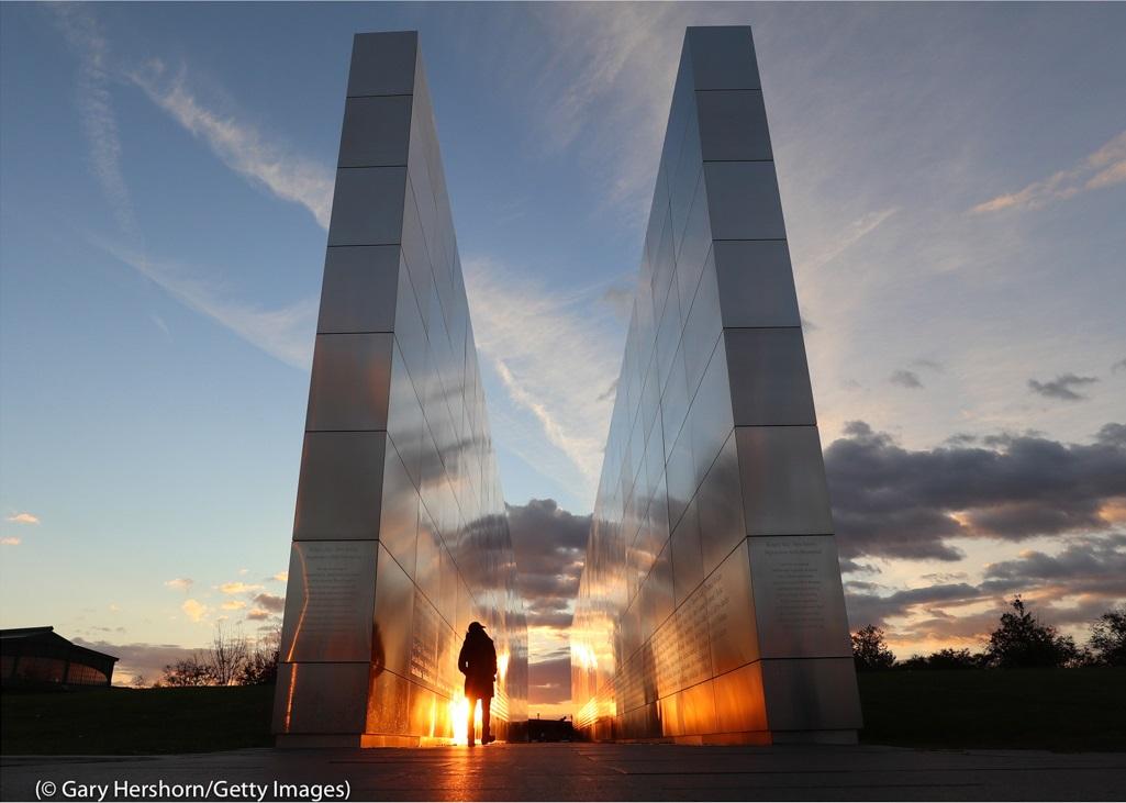 ニュージャージー州ジャージーシティのリバティ州立公園。夕暮れの中、慰霊碑「エンプティ・スカイ・メモリアル」の間を人が歩いている。