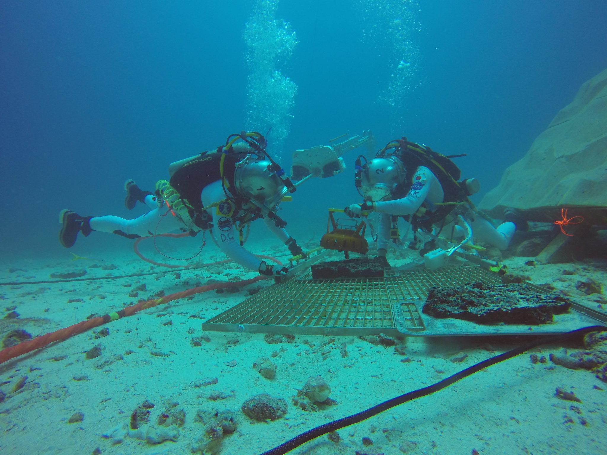 サンプル採集時に本体を安定させるため、ジェット推進研究所が開発した固定装置を岩石に取り付けるクルー (Photo courtesy of NASA)