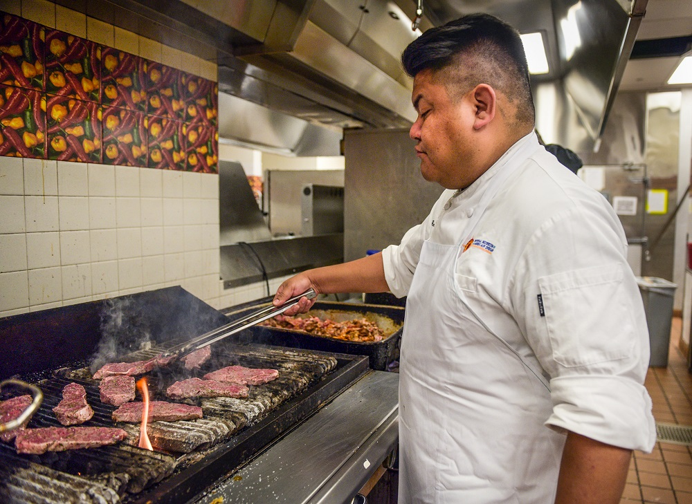 Bitsoie cooks meat in the kitchen of Mitsitam Native Foods Café. (© Carol Guzy)