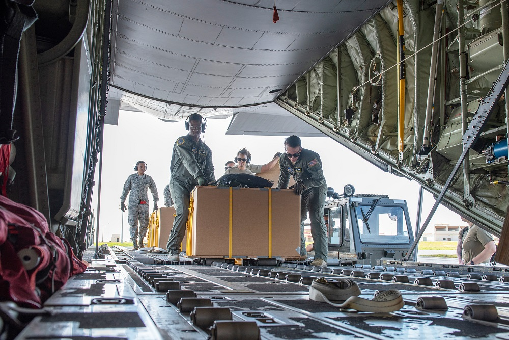 Staff Sgt. Deondre Rogers, left, and Senior Airman Toby Hayes, right, both 36th Airlift Squadron loadmasters out of Yokota Air Base, Japan, load a Low-Cost, Low-Altitude practice bundle onto a C-130J Super Hercules as part of Operation Christmas Drop 2019. (Photo by Senior Airman Matthew Gilmore)