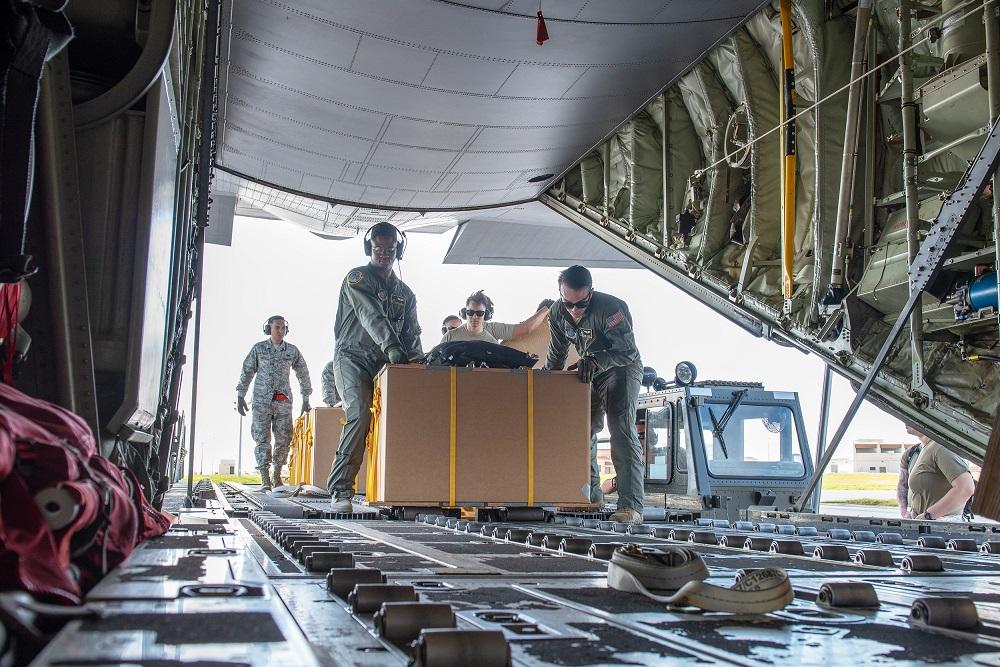 2019年クリスマス・ドロップ作戦の一環として、低コスト低高度物資をC-130Jスーパーハーキュリーズ輸送機に積む横田基地第36空輸中隊機上輸送係デオンドル・ロジャース二等軍曹(左)とトビー・ヘイズ上級空兵(右)(写真提供:マシュー・ギルモア上級空兵)