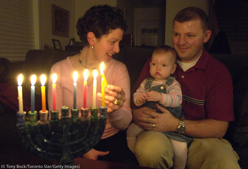 A family lights a menorah, one candle represents each night of Hanukkah. (© Tony Bock/Toronto Star/Getty Images)