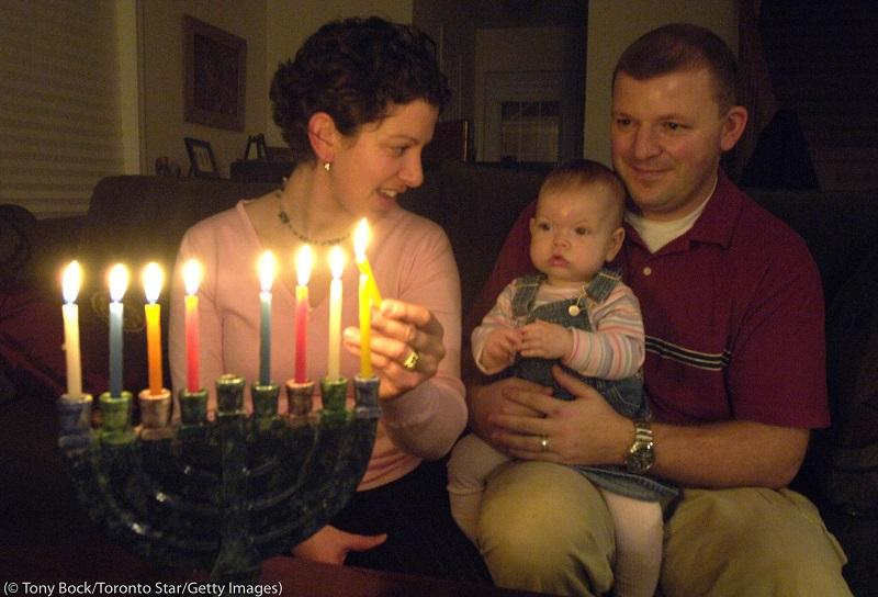 メノラー(燭台)に灯をともす家族。1本のキャンドルが8日間のハヌカ祭りの1日を意味する (© Tony Bock/Toronto Star/Getty Images)