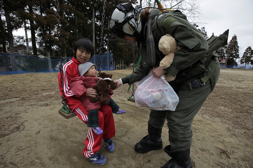 "A Navy helicopter pilot presents a teddy bear to a baby in Kesennuma, Miyagi Prefecture, during ""Operation Tomodachi"" to deliver supplies to evacuees in an earthquake and tsunami devastated area in 2011. (AP Photo/Eugene Hoshiko)"