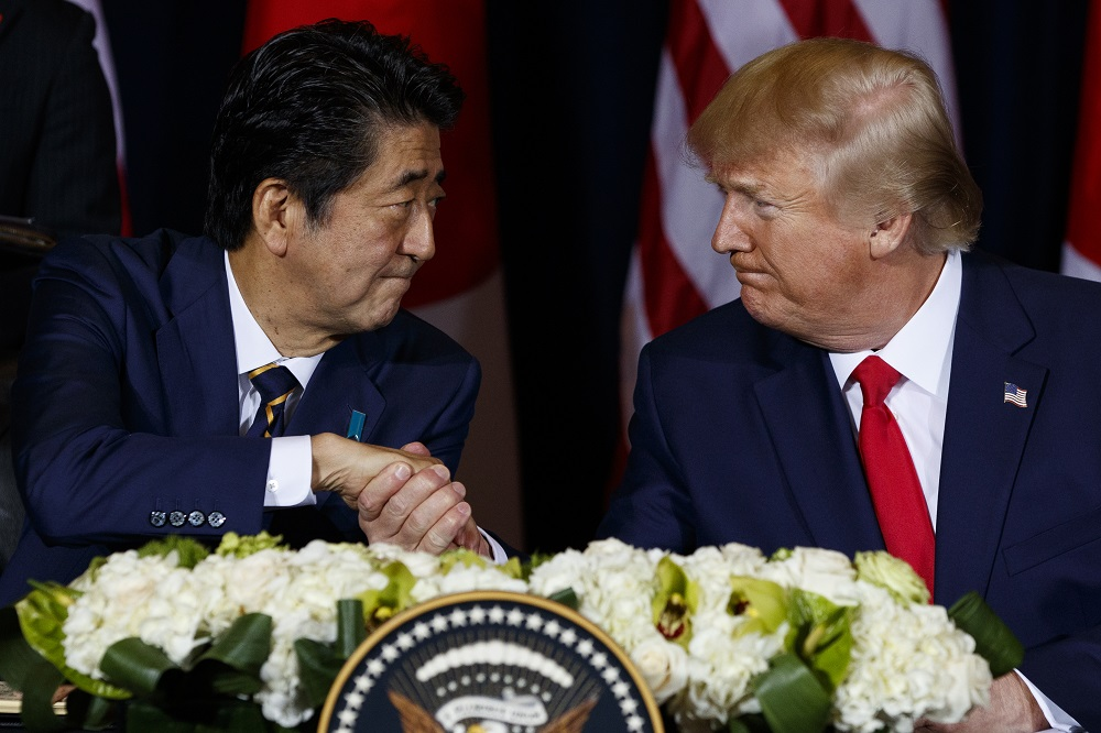 President Donald Trump shakes hands with Prime Minister Shinzo Abe before signing a trade agreement during the United Nations General Assembly session, in New York in 2019. (AP Photo/Evan Vucci)