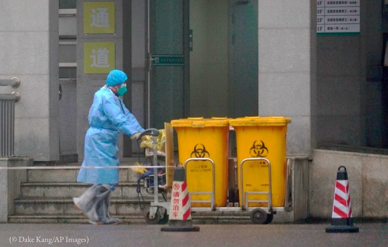 A staff member moves biomedical waste containers past the entrance of the Wuhan Medical Treatment Center, where some people infected with a new virus are being treated, in Wuhan, China, January 22. (© Dake Kang/AP Images)