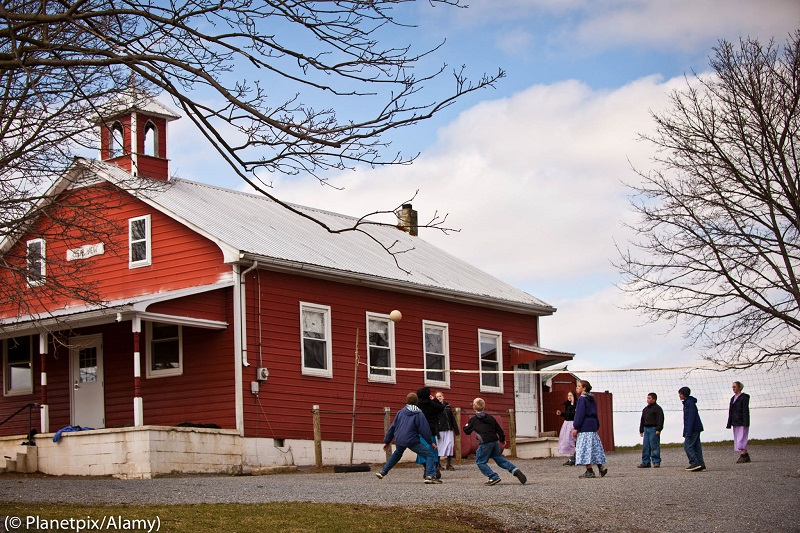 Amish children play volleyball outside their one-room schoolhouse in Pennsylvania. The Amish often do not go to school beyond the eighth grade. (© Planetpix/Alamy)