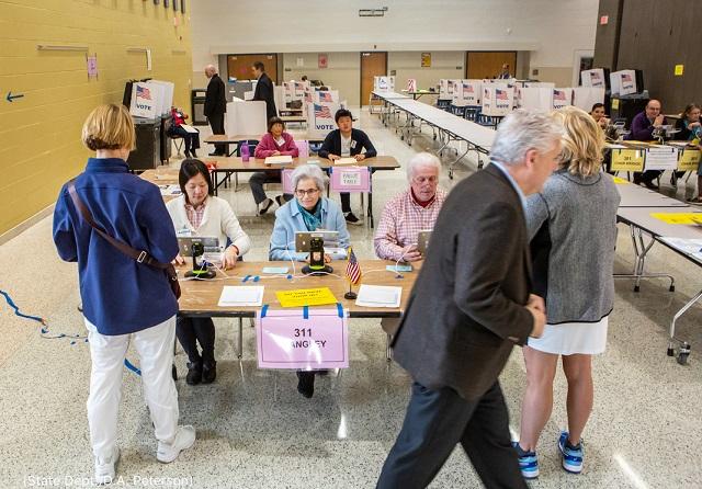 スーパーチューズデーに有権者の投票手続きをする選挙スタッフ。バージニア州マクリーンのラングリー高校にて (State Dept./D.A. Peterson)