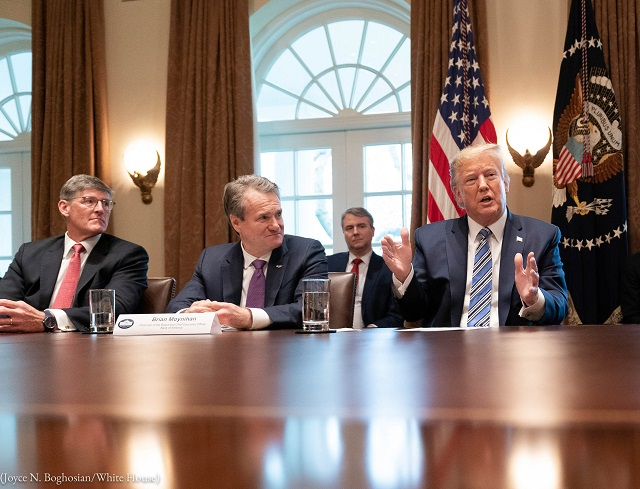 Citigroup chief executive Michael Corbat (left) and Bank of America chief executive Brian Moynihan (center) listen to President Trump at a meeting to discuss the coronavirus response on March 11 in Washington. (Joyce N. Boghosian/White House)