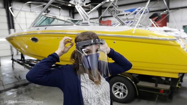 Romy Humphries wears a face mask and shield March 26 at SugarHouse Industries, a Utah manufacturer of boat tops and covers. (© Rick Bowmer/AP Images)