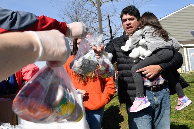 メリーランド州アナポリスの移動配給所で3月16日、学校に行けない生徒ための無料の食事を受け取る住民 (© Susan Walsh/AP Images)