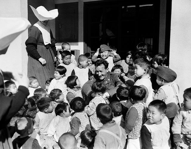 子どもたちに囲まれるオライリー軍曹 (© AP Images)