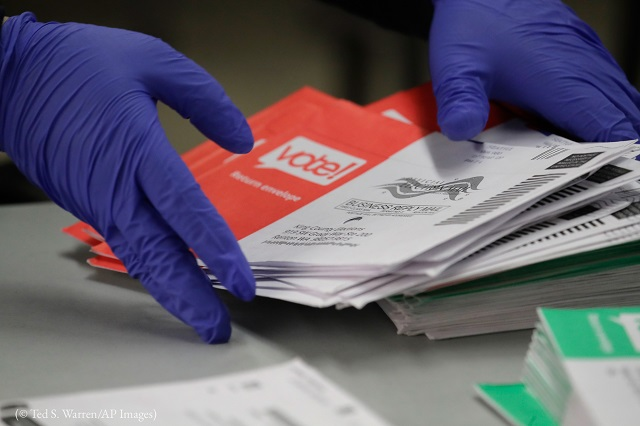 An election worker in Renton, Washington, handles ballots from the Washington state presidential primary election on March 10. (© Ted S. Warren/AP Images)