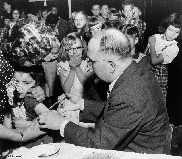 On April 25, 1955, Patsy Murr, a first-grader in Lancaster, Pennsylvania, is vaccinated against polio by Dr. Norman E. Snyder as classmates react. (© AP Images)