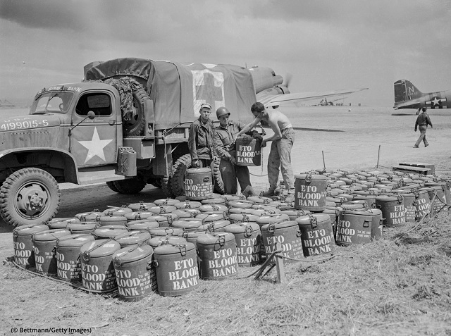 第2次世界大戦中、臨時駐機場の人員運搬車前で、献血された血液のドラム缶を集める米軍兵士 (© Bettmann/Getty Images)