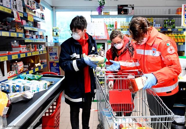 イタリア中部で自宅から出られない高齢者に届ける物資を購入する赤十字のボランティア (© Jennifer Lorenzini/LaPresse/AP Images)